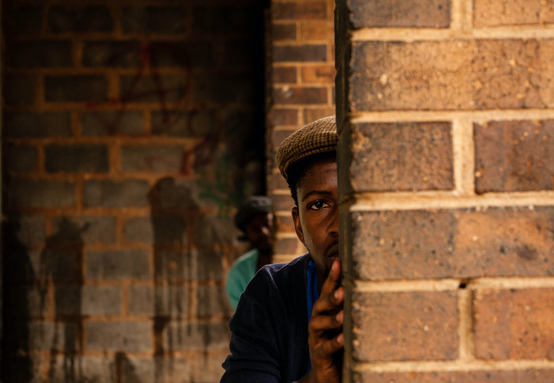black scared men hiding behind shabby brick walls
